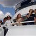 Happy passengers standing at the front of the second deck of charter yacht Miss Toronto